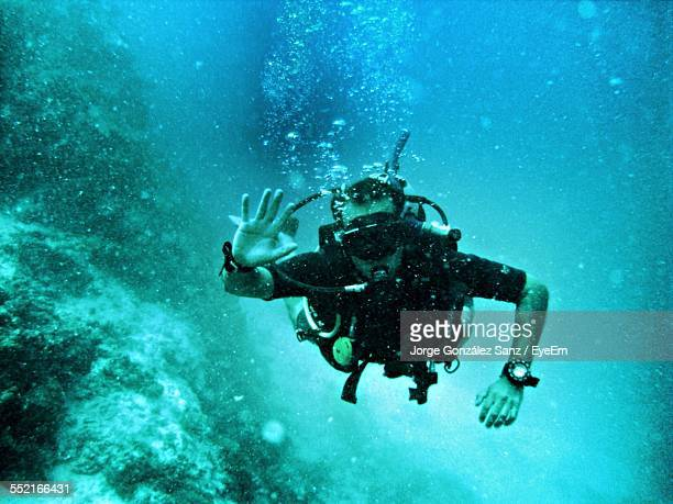 man waving underwater - waving gesture stock photos and pictures