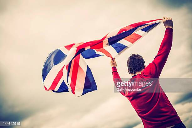 man waving union jack flag - union jack stock photos and pictures