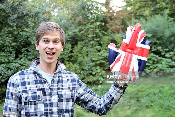 man waving with a novelty union jack hand - foam hand stock photos and pictures