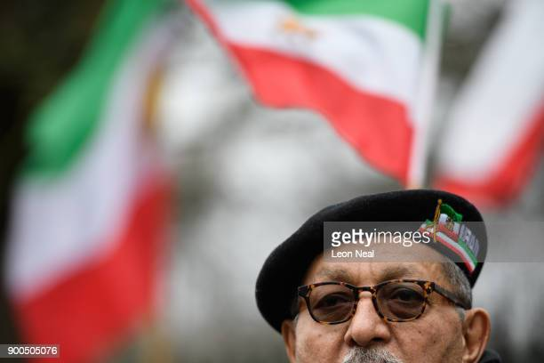 A man weaing an Iran beret stands with antiregime protestors as they demonstrate outside the Iranian embassy on January 2 2018 in London England...