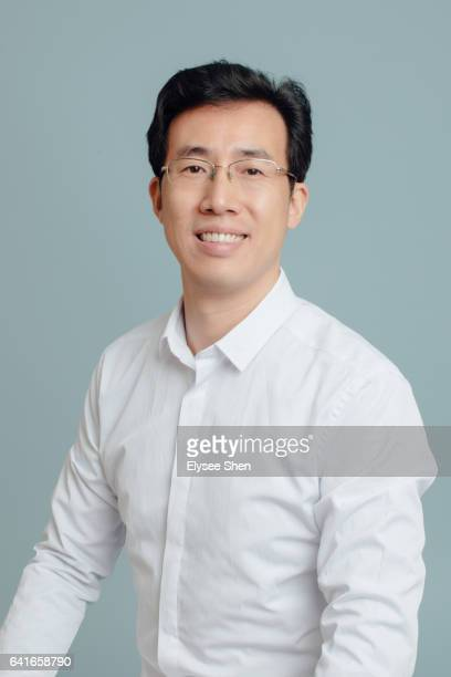 man wear a white shirt on a blue background - 白いシャツ ストックフォトと画像