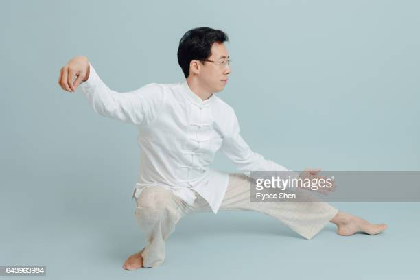 man wear chinese clothing playing tai chi on a blue background - kung fu stock photos and pictures