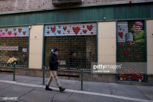 A man wear protective mask walks near closed shop in Via Barbaroux on November 24 2020 in Turin Italy Via Barbaroux is an old area in Turin which has...