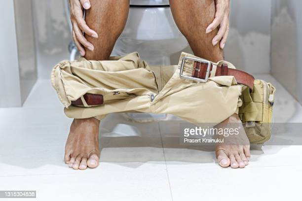 man wear yellow pants sitting in toilet - hemorrhoids stock pictures, royalty-free photos & images