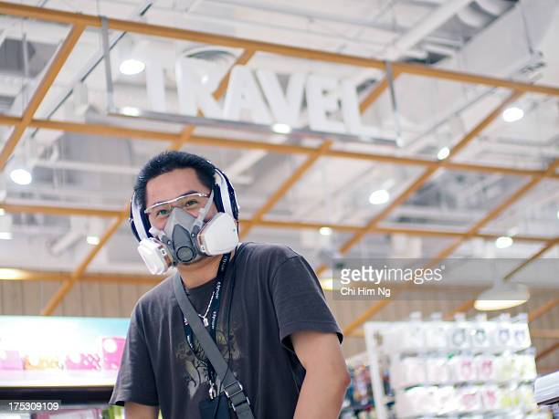 CONTENT] A man wearing 3M oral nasal mask used for spray painting He is also wearing over the ear Soul headphone and a pair of eyeglasses Behind is a...