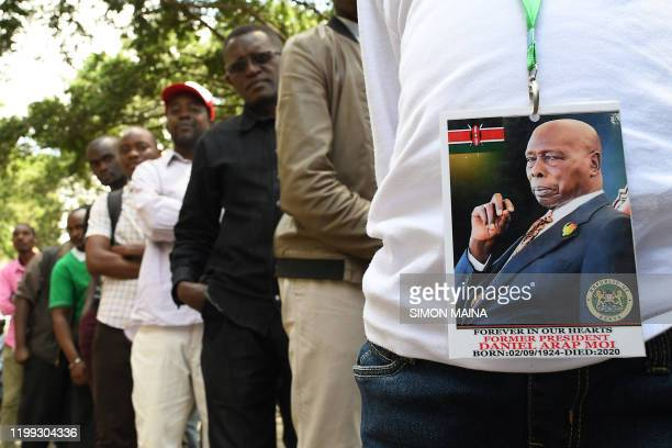 A man wearing a badge with the photo of late former Kenya's President Daniel Arap Moi queues to view his remains outside Parliament Buildings where...