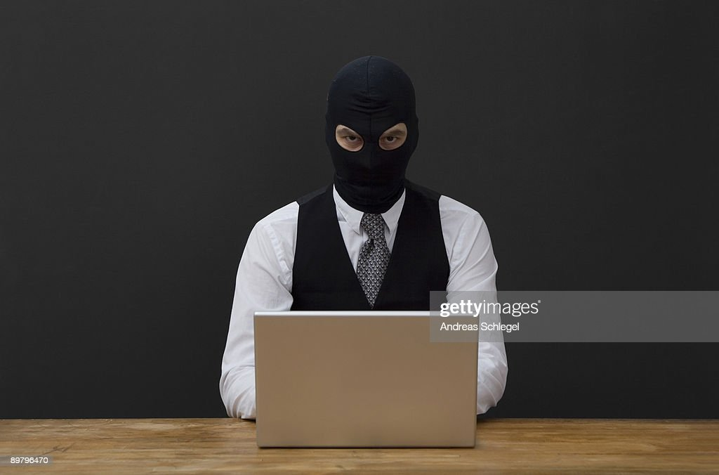 A man wearing a  balaclava and using a laptop : Stock Photo