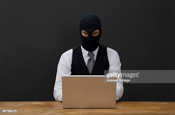 a man wearing a  balaclava and using a laptop - balaclava stock pictures, royalty-free photos & images