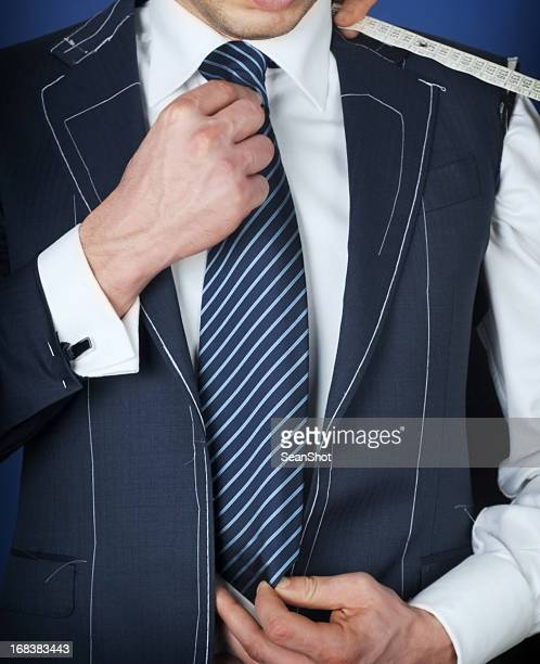 man wearing a black coat, white suit and striped blue tie.  - customised stock pictures, royalty-free photos & images