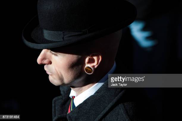 A man wearing a bowler hat and ear gauge leaves following the annual Remembrance Sunday memorial on November 12 2017 in London England The Prince of...