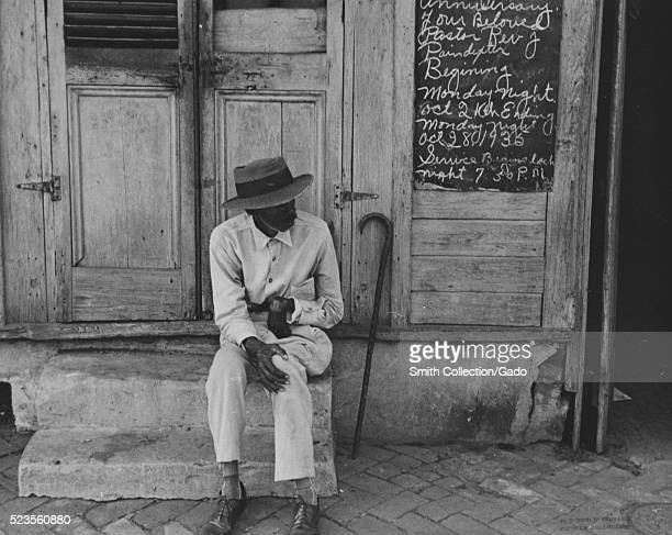 A man wearing a button down shirt and a hat is sitting on the concrete steps of a church a sign advertising the times for church services celebrating...