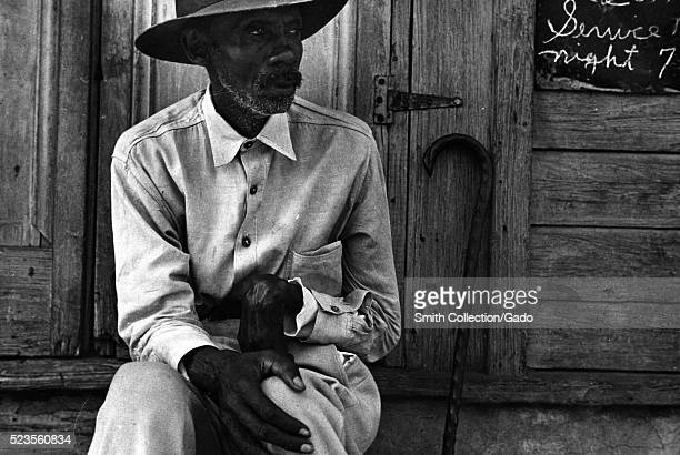 A man wearing a button down shirt and a hat is sitting on the steps of a church a sign advertising the times for church services hangs on the side of...