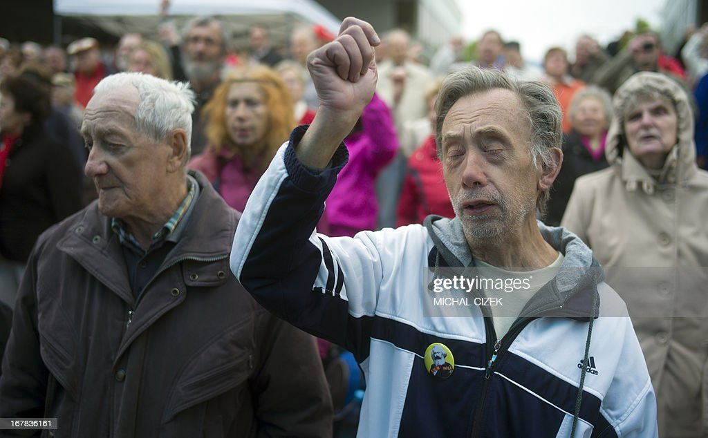 A man wearing a button of revolutionary socialist Karl Marx sings along with other supporters of the Czech opposition Communist party (KSCM) the International, the most famous communist song, as they celebrate May Day on May 1, 2013 in Prague. PHOTO