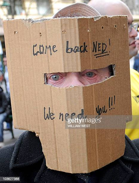 A man wearing a cardboard helmet stating 'Come back Ned' in reference to famous Australian outlaw Ned Kelly urges people not to vote as they queue at...
