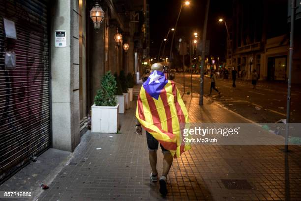 A man wearing a Catalan flag is seen walking down a street after attending a protest in Plaza Universitat during a regional general strike to protest...