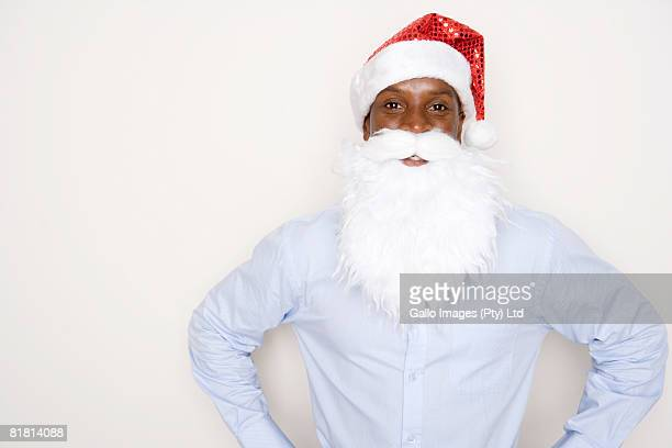 Man wearing a Christmas hat and fake Father Christmas beard, hands akimbo.