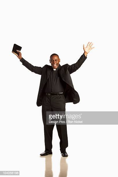 A Man Wearing A Clerical Collar And Holding A Bible With Hands Raised