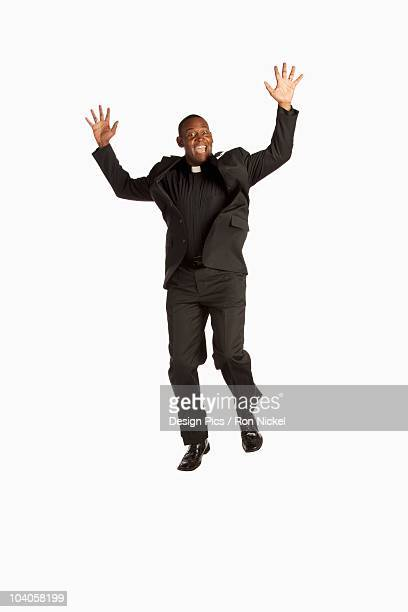 a man wearing a clerical collar and jumping in the air - vicar stock pictures, royalty-free photos & images