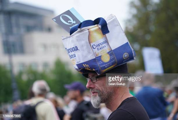 A man wearing a Corona beer bag and a Querdenker Q flag attends a gathering of coronavirus skeptics on the eve of a planned protest march on August...