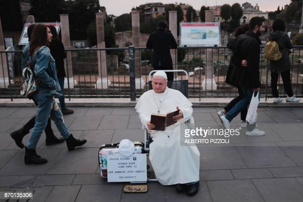 A man wearing a costume of late Pope John Paul II performs on a street in Rome on November 4 2017 / AFP PHOTO / Alberto PIZZOLI