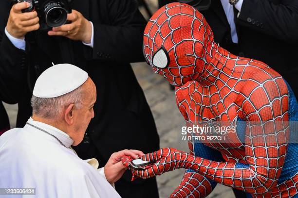 Man wearing a costume of the Spider-Man fantasy character, who performs in hospitals for sick children, hands a Spider-Man mask to Pope Francis as...