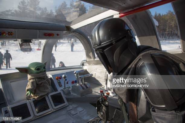 Man wearing a costume of the StarWars protagonist Din Djarin poses onboard a giant replica of the Razor Crest, a a gunship from the StarWars spinoff...
