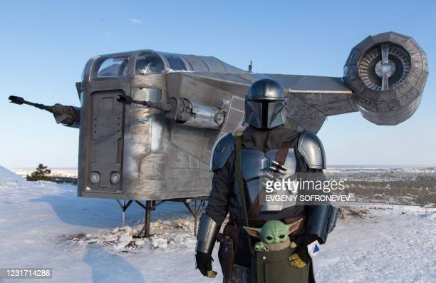 Man wearing a costume of the StarWars protagonist Din Djarin poses in front of a giant replica of the Razor Crest, a gunship from the StarWars...