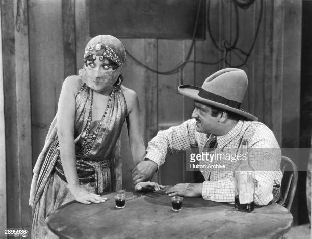 A man wearing a cowboy hat angrily grabs the wrist of a woman wearing a veil in an unidentified still from a silent Western film The man sits in a...