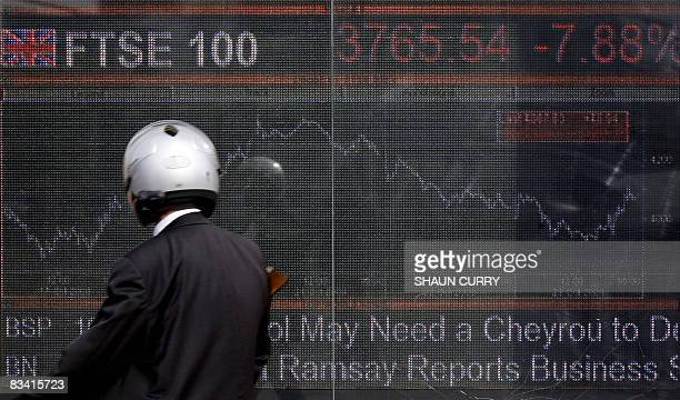 A man wearing a crash helmut is pictured beside an electronic display board showing the FTSE 100 share index in London on October 24 2008 Stock...