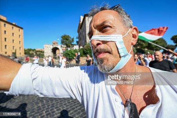 "Man wearing a cut out face mask takes part in a protest of ""No Mask"" movements, Covid deniers movements, anti-5G movements and anti-vaccination..."