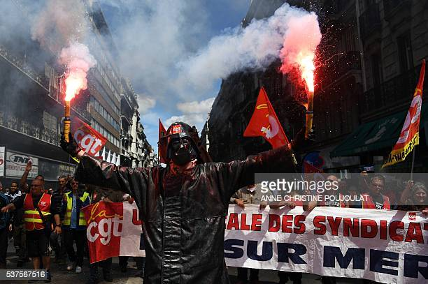 A man wearing a Dark Vador mask holds smoke flares during a demonstration against the French government's planned labour law reforms on June 2 2016...
