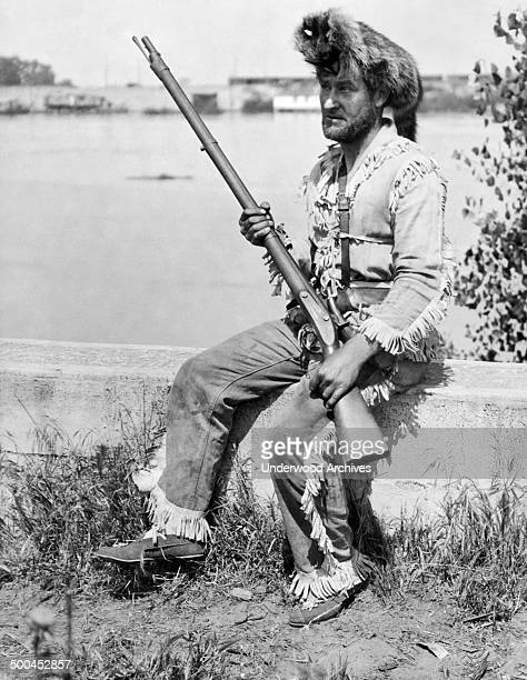 A man wearing a Davy Crockett outfit with a coonskin cap and a musket circa 1928