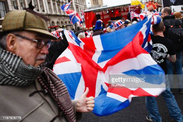 Man wearing a deerstalker hat, iconic of Sir Arthur Conan Doyle's fictional Victorian detective Sherlock Holmes, passes Brexit supporters waving a...