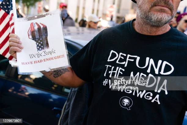 """Man wearing a 'Defund the Media' QAnon shirt is seen at a """"Stop the Steal"""" rally against the results of the U.S. Presidential election outside the..."""