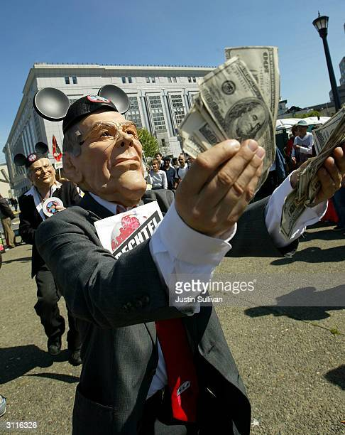A man wearing a Donald Rumsfeld mask holds one hundred dollar bills during an antiwar demonstration to mark the oneyear anniversary of the Iraq war...