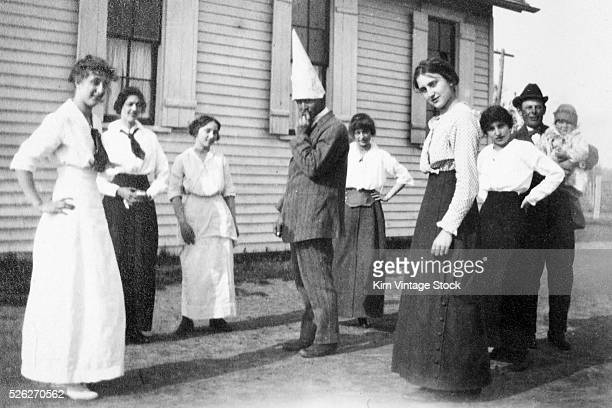 A man wearing a dunce cap is surrounded by women