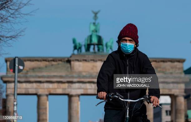 Man wearing a face cover cycles in front of the Brandenburg Gate in Berlin on April 10 amid a new coronavirus COVID-19 pandemic.