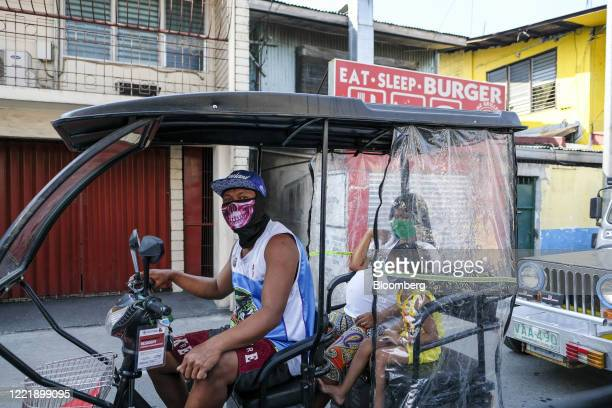 Man wearing a face covering drives a motorized tricycle as a pregnant woman and a girl ride in the backseat in Taguig City, Metro Manila, the...