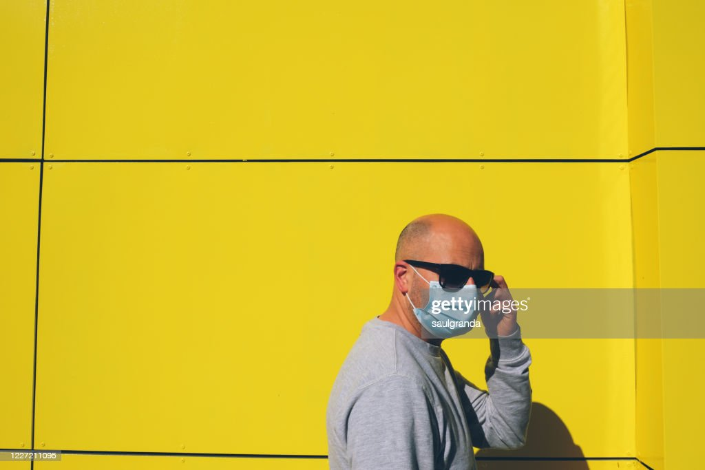 Man wearing a face mask against yellow wall : Stock Photo
