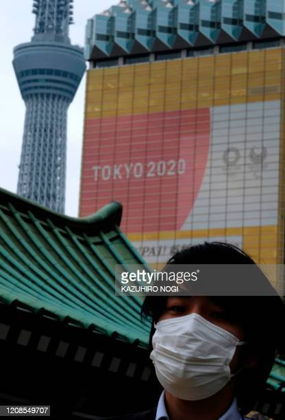 A man wearing a face mask amid concerns of the COVID19 coronavirus walks before the logo of the Tokyo 2020 Olympic Games in Tokyo on March 30 2020...