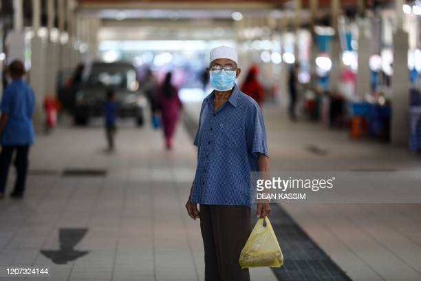 Man wearing a face mask, amid concerns over the spread of the COVID-19 coronavirus, holds a plastic bag of goods at the Gadong Night Market in Bandar...