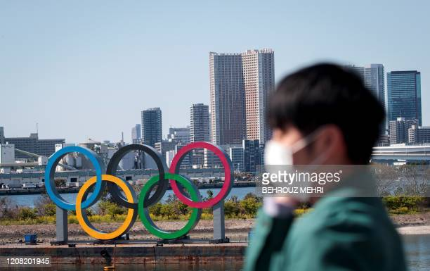 Man wearing a face mask, amid concerns over the spread of the COVID-19 novel coronavirus, stands before the Olympic rings from an observation point...