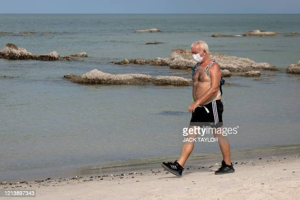 Man wearing a face mask, amid concerns over the spread of the COVID-19 coronavirus, walks along Hua Hin beach in Thailand on May 19, 2020. -...