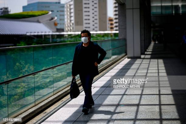 Man wearing a face mask amid concerns over the spread of the COVID-19 coronavirus walks through Shinagawa Intercity office buildings in Tokyo on May...