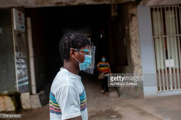 Man wearing a face mask and face shield walk in Maputo on February 6, 2021. - About two million Mozambicans in the epicenter of the country's...