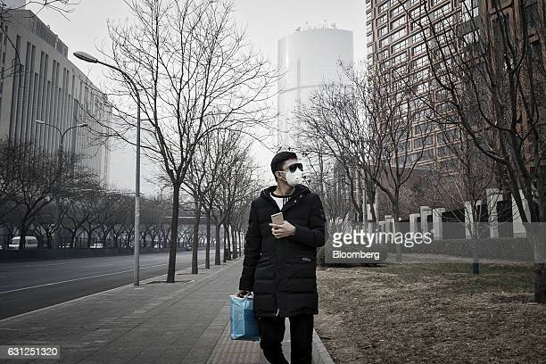 A man wearing a face mask and sun glasses walks down a street in Beijing China on Friday Jan 6 2017 Toxic haze that settled over much of China during...