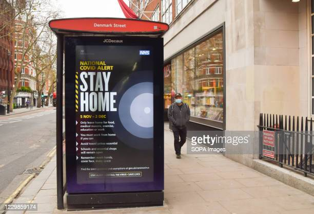 Man wearing a face mask as a precaution against the spread of covid-19 walks past a Stay Home sign at a bus stop on Charing Cross Road. England is...