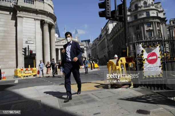 A man wearing a face mask as a precaution against the transmission of the novel coronavirus walks near the Royal Exchange and the Bank of England in...