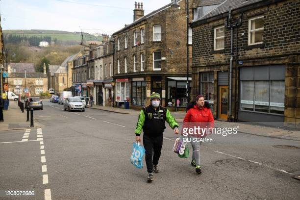 Man wearing a face mask as a precautionary measure against covid-19, and a woman carrying a pack of toilet rolls, walk through the centre of Marsden...