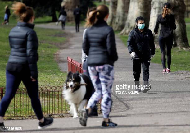 A man wearing a face mask as a precautionary measure against Covid19 walks to get his daily exercise allowance in Battersea Park in London on March...